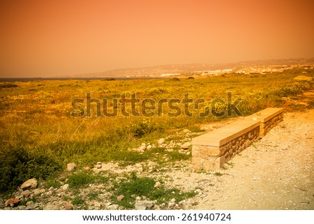 Stone seat on mountain above the sea on a background of the sky and city. - stock photo