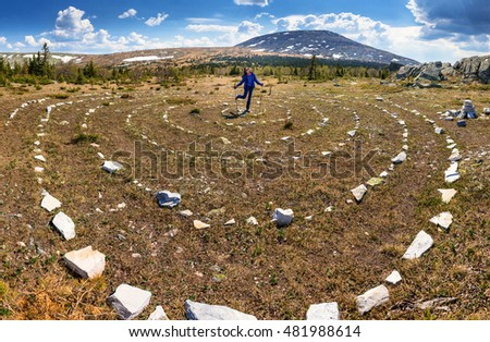 Stone spiral on the field at mountain with woman hiker