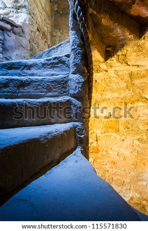 Stone Spiral Stairway with mixed light in the Castle - stock photo