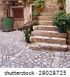 Stone staircase with plants in a medieval city with cobblestone pathways - stock photo