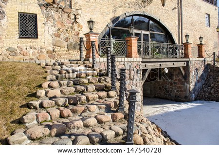 stone staircase with steel railings and light lamp leading to retro manor and snow remain in spring.  - stock photo