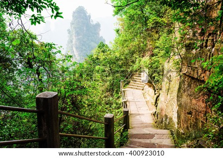 Stone stairs leading along steep cliff in the Tianzi Mountains (Avatar Rocks), the Zhangjiajie National Forest Park. Walkway among green foliage. Quartz sandstone pillars are visible in background. - stock photo