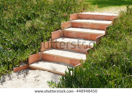 Stone stairs on a beach with sand and green plants on both sides - stock photo