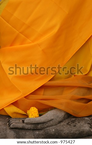 Stone statue of Buddha wrapped in orange fabric in Nakhon Pathom, Thailand - stock photo