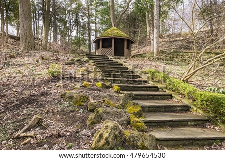 Stone steps lead up to a old octagon shelter with a green moss covered roof in a forest.