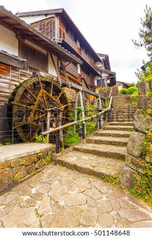 Stone steps next to traditional waterwheel in historic restored town of Magome on the ancient Nakasendo trail on an overcast day in Japan. Vertical