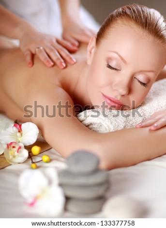 Stone therapy. Woman getting a hot stone massage - stock photo