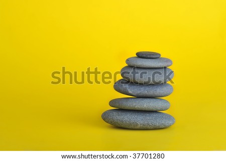 stone tower isolated on yellow background - stock photo