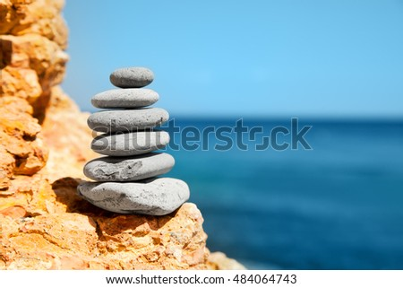 Stone tower on rocks against the sea. Concept for rest, spa, relaxation, resorts and summer holidays.