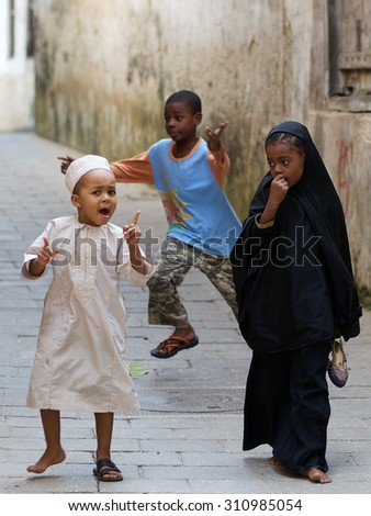 STONE TOWN, ZANZIBAR - JULY 03, 2014. Local children on a typical narrow street in Stone Town.