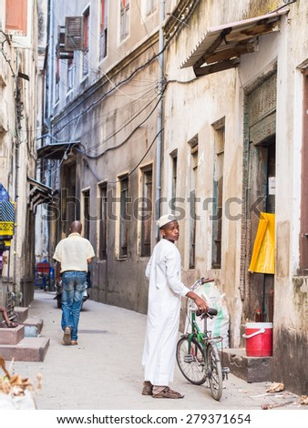 STONE TOWN, ZANZIBAR - MAY 02, 2015: Local people walking on one of the narrow streets in old part of Stone Town, Zanzibar in East Africa. Vertical orientation, wide angle.