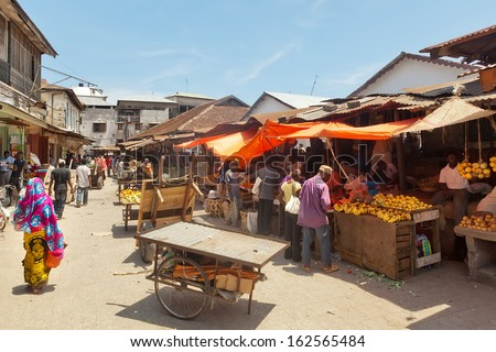 STONE TOWN, ZANZIBAR/TANZANIA - APRIL 4: City market under bright sun with sellers and buyers shown on 4 April 2012 in Zanzibar, Tanzania. - stock photo
