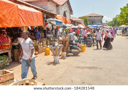 STONE TOWN, ZANZIBAR/TANZANIA - APRIL 4 2012: Old Town Market under bright sun with sellers and buyers. This is a classic Swahili public space, mixing architectural and cultural influences.