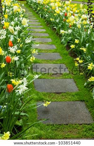 Stone walk way winding in flower garden - stock photo