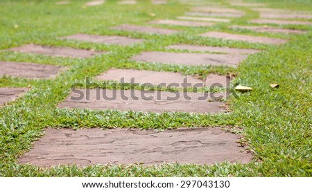 Stone walkway on th green grass in the park - stock photo