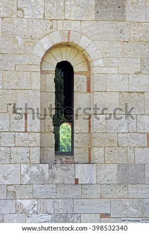 Stone wall and window of the Abbey of Sant'Antimo, near Montalcino, Tuscany, Italy       - stock photo