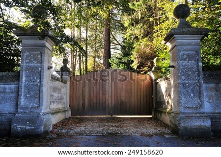 Stone Wall and Wooden Gateway of a Country Estate - stock photo
