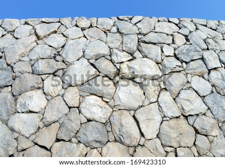 Stone wall background and texture with blue sky - stock photo