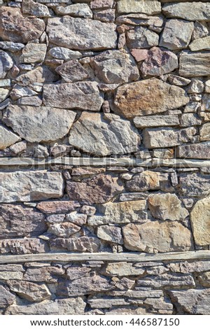 Stone wall background with wooden beams closeup