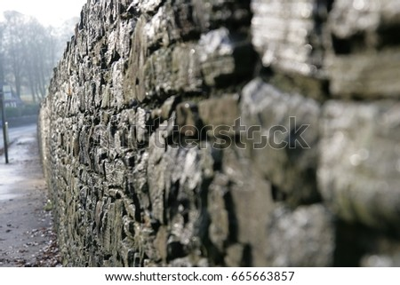 Stone wall by road