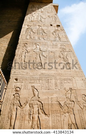 stone wall of Egyptian Edfu Temple of falcon god Horus, with carving figures and hieroglyphs, ceremony people, priest, pharaoh or king, goddess or queen, in Egypt, Africa - stock photo