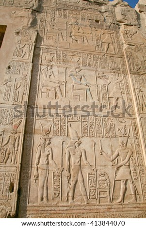 stone wall of Egyptian Kom Ombo Temple, with carving figures and hieroglyphs, with ceremony people, priest, pharaoh or king, goddess or queen, in Egypt, Africa - stock photo