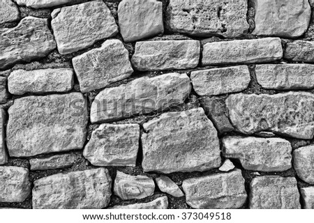 stone wall of large stones, black and white - stock photo