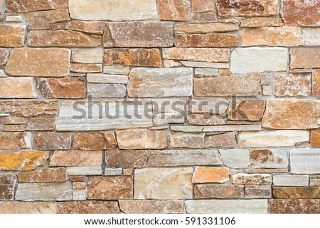 Stone wall natural stones different sizes stock photo for Rustic brick veneer