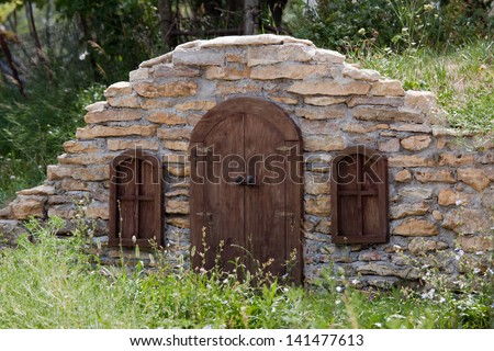 Stone Wall of Root Cellar with Small Door and Windows or Hobbit House in a Hillside