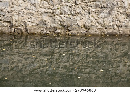 stone wall reflection on the river water with small leaves floating. Textured Background.