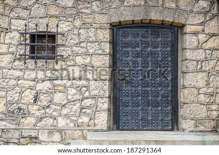 stone wall texture background with ancient door to the church and small window - stock photo