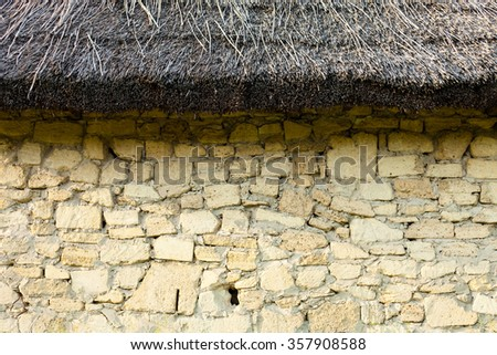 Stone wall under the straw-thatched roof. Old Ukrainian architecture. - stock photo