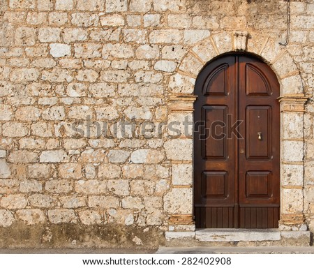 Stone wall with a door. The wall of an old house in Europe with the front door. Background texture of large stone bricks. Ancient wooden door in stone castle wall. Southern Italy. Europe. - stock photo
