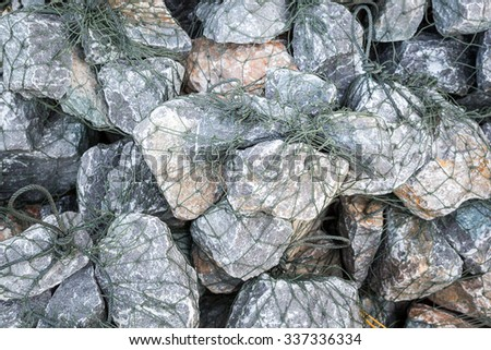 Stone wall with wire mesh.