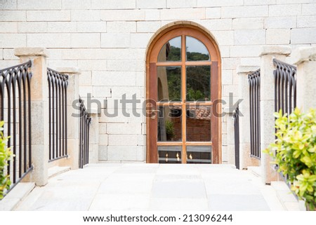 Stone wall with wooden door - stock photo
