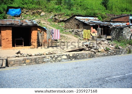 Stone walled-tin roofed huts-laundry hanging from a wire by the side of the Prithvi Highway near Aanbu Khaireni village. Tanahu distr.-Gandaki zone-Nepal. - stock photo