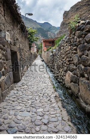 Stone walls, buildings, alley and canal in Ollantaytambo, Inca city of Sacred Valley, major travel destination in Cusco region, Peru. - stock photo