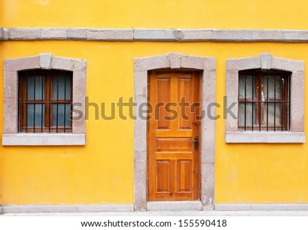 Stone window and door on Yellow wall background house fasade - stock photo