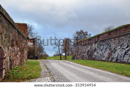 Stone winter cobble  rustic street in a retro  Finland  northern style landscape.