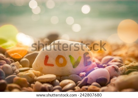 Stone with LOVE text on Sea Background. Filtered Photo with Bokeh. Romantic Travel Concept. - stock photo