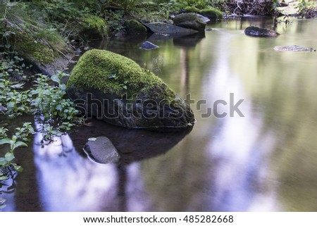 Stone with moss and flowing river.