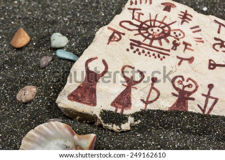 stone with petroglyphs on the sand, surrounded by sea shells - stock photo