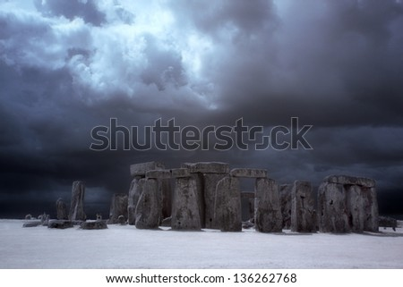 Stonehenge historic site on green grass under blue sky. Stonehenge is a UNESCO world heritage site in England with origins estimated at 3,000BC - stock photo