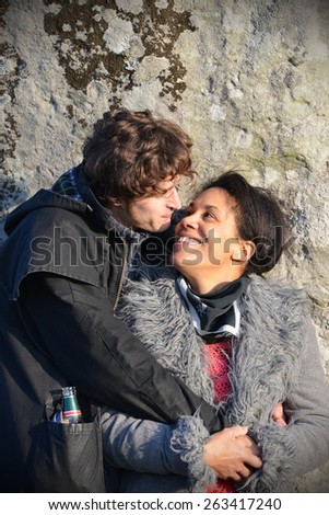 STONEHENGE - MAR 20: A couple embraces while celebrating the spring equinox at the ancient standing stones on Mar 20, 2014 in Stonehenge, UK. The world famous landmark dates back to 2600 BC. - stock photo