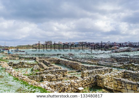 Stones and Greek ruins on the grass covered with snow