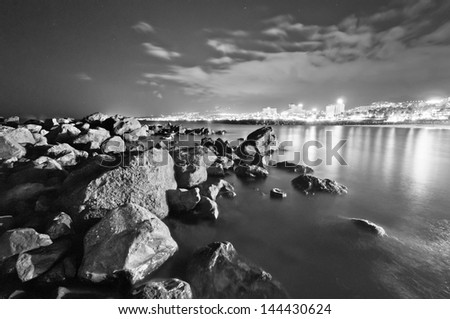 Stones and ocean at night in black and white - stock photo