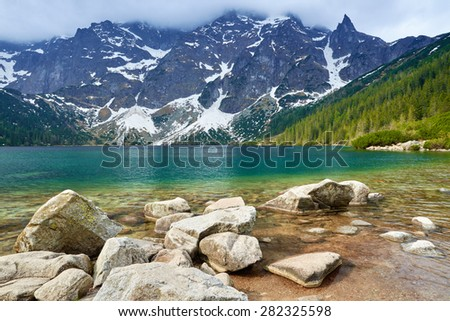 Stones at a shore of the Morskie Oko lake in the High Tatra Mountains. National park, Carpathians, Poland. - stock photo
