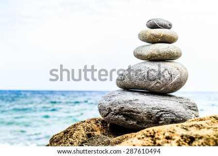 Stones balance and wellness retro spa concept, inspiration beautiful landscape background, zen-like and well being tranquil composition. Closeup creative dark stable stones stack on rock over blue sea - stock photo