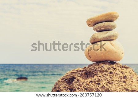 Stones balance and wellness retro spa concept, inspiration, zen-like and well being tranquil composition. Close-up of white pebbles stack over blue sea - stock photo