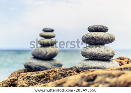 Stones balance and wellness retro spa concept, peaceful and unique inspiration, zen-like and well being tranquil composition. Closeup of white pebbles stack over blue sea - stock photo